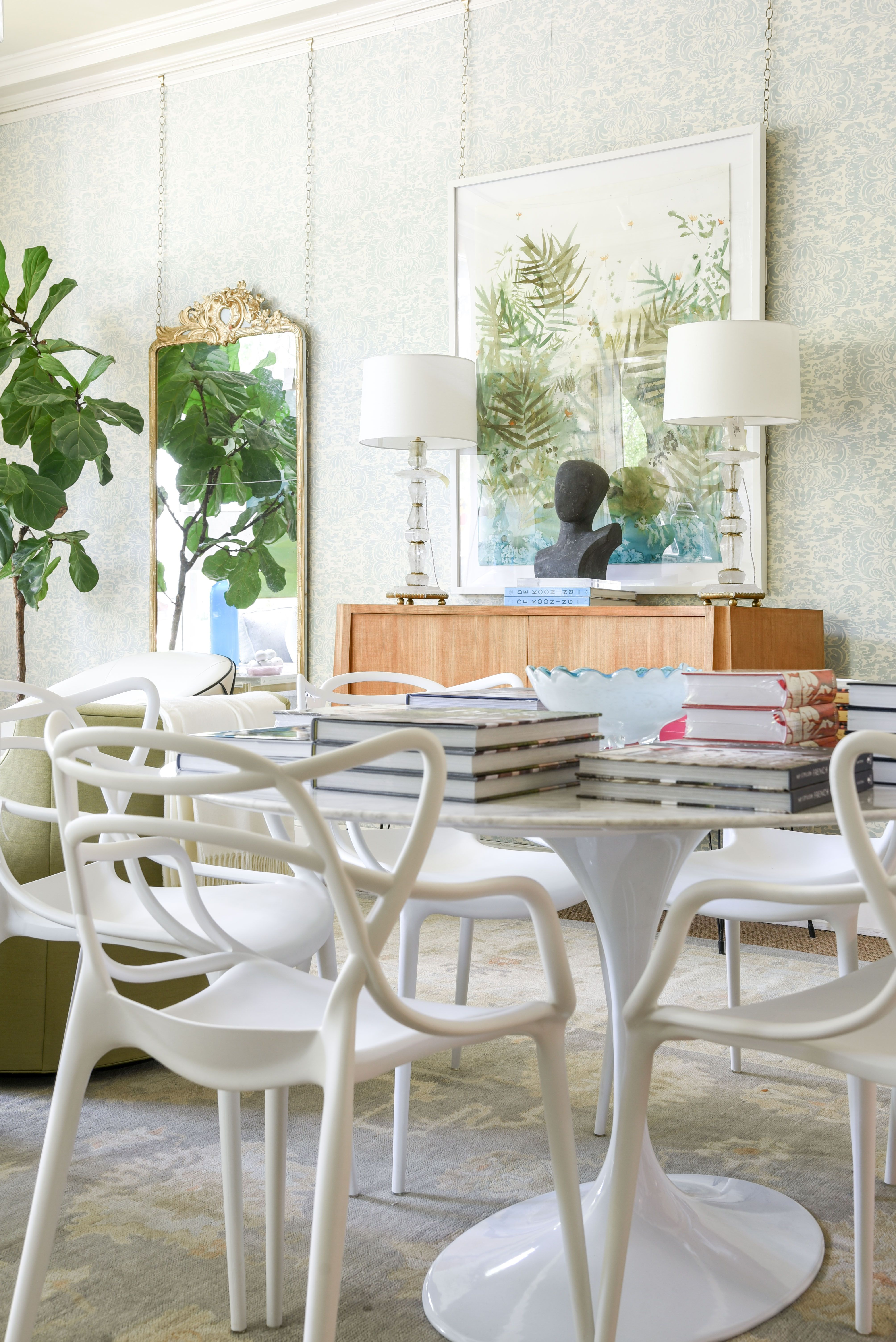 marble dining table with tulip base and unique white chairs