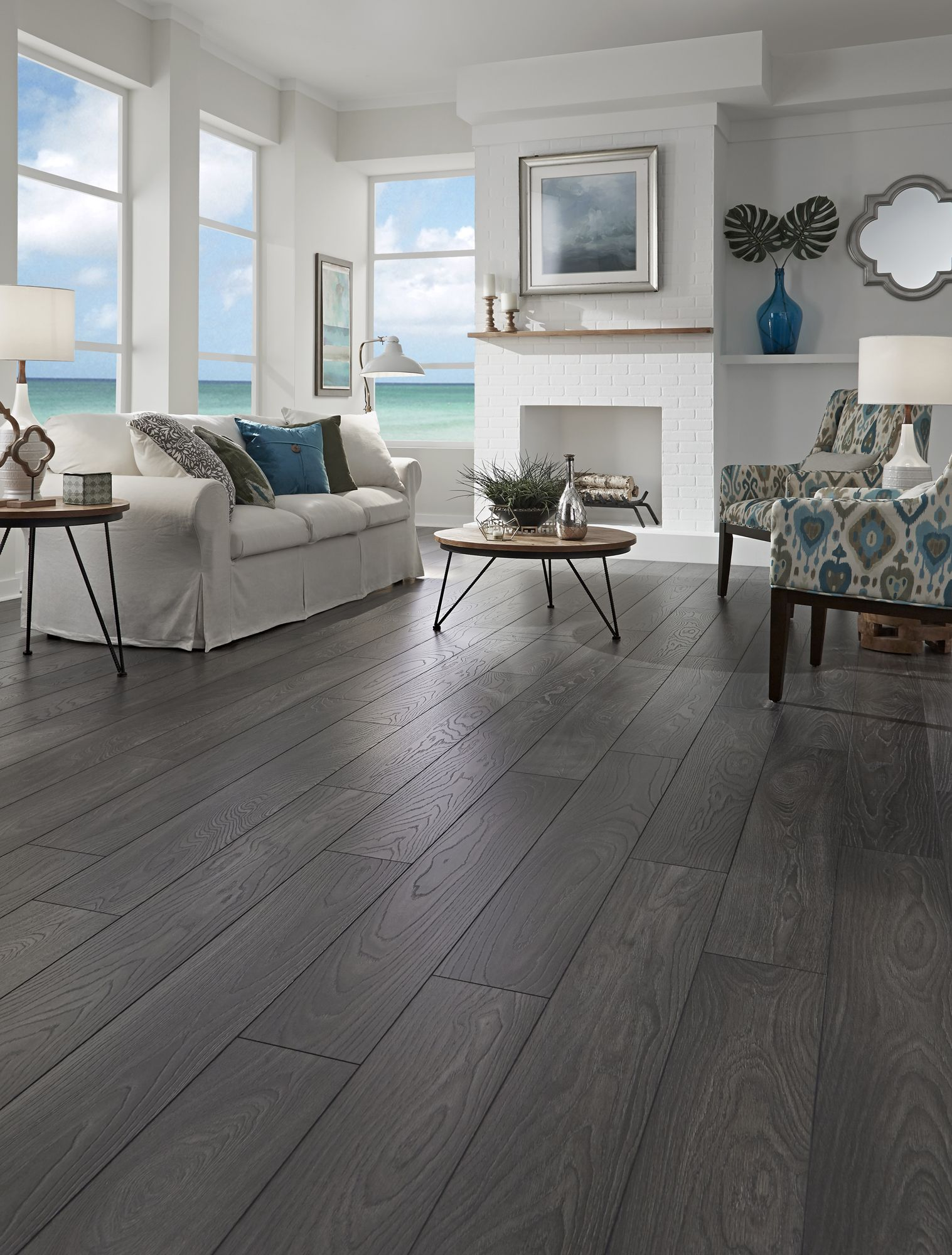 Seaside Grays Create A Feeling Of Relaxed Living Carbon Oak Laminate Has A Wirebrushed Texture Grey Laminate Flooring Home Grey Laminate Flooring Living Room