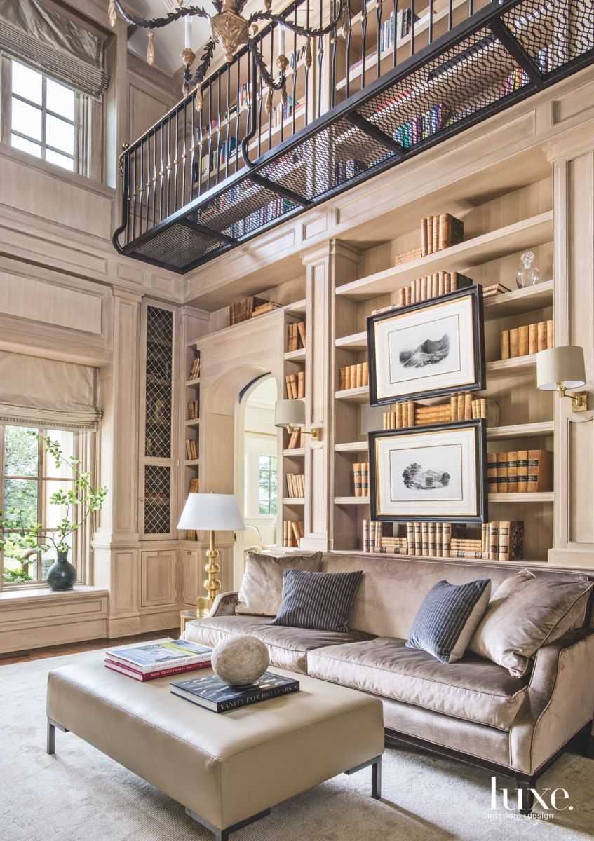 The double-height library, modeled after the Library of Trinity College Dublin, features intricate white-oak paneling and a metal upper balcony. The sofa is from Kasler's collection for Hickory Chair. Kary Cabinets executed the bookshelves and paneling, and Taylored Iron built the balcony.