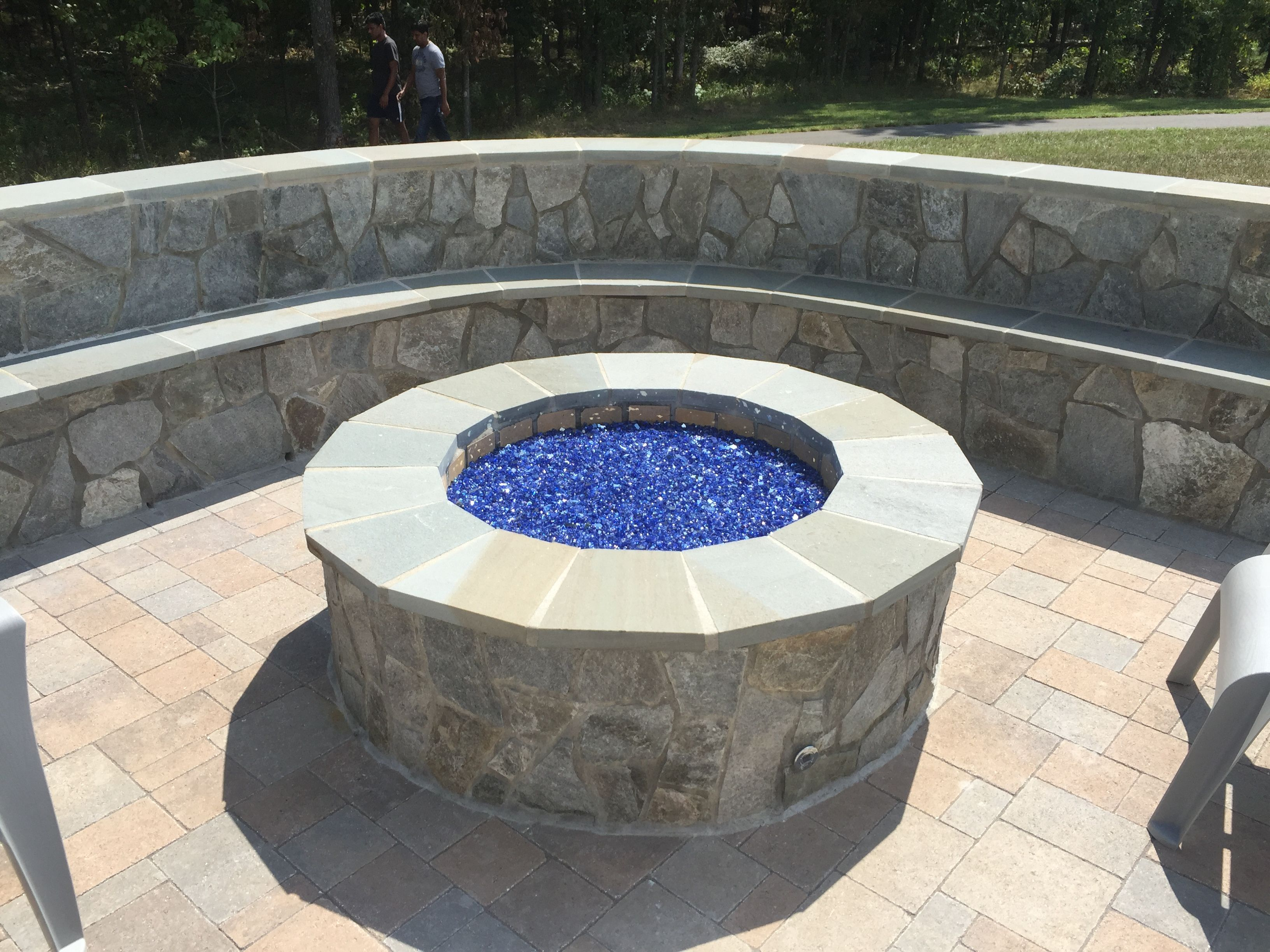 A Hanover Paver Patio With A Stone Seating Bench And Gas