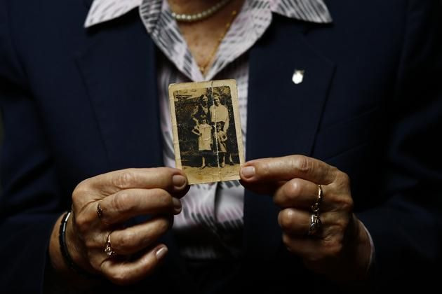 Auschwitz death camp survivor Maria Stroinska, 82, holds a family photo taken before the war, as she poses for a portrait in Warsaw January 12, 2015. Stroinska was 12-years-old during the Warsaw Uprising when she and her sister were sent from their house to a camp in Pruszkow before she was moved alone by train to Auschwitz-Birkenau.