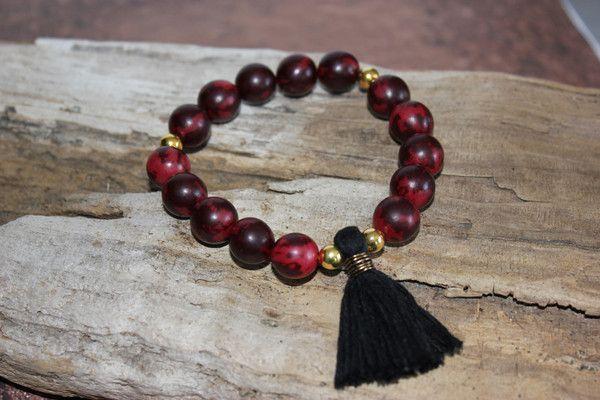 Bracelet ''Retour a la Source ''  Bracelet fait de bois exotique de couleur rouge avec insertion de billes de couleur or et un ''tassel'' noir..