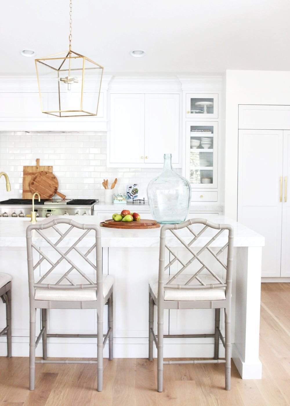 White kitchen with light gray Ballard Designs bar stools and brass ...