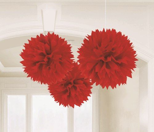 Red pom poms make an effective ceiling decoration at Christmas time