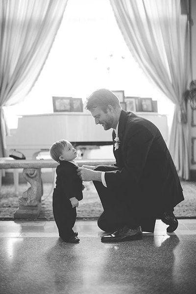 Machen Sie ein Foto vom Bräutigam, der die Krawatte Ihres kleinen Mannes repariert. – Aussenseiter – Ringe