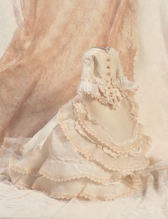 """Theriault's Antique Doll Auctions - For 1870's-era 17"""" poupee The three piece ensemble of sheer muslin has fitted jacket,skirt with very full back and extended train,and detachable front skirt with tiers of lace and ruffle. Excellent condition. Circa 1870."""