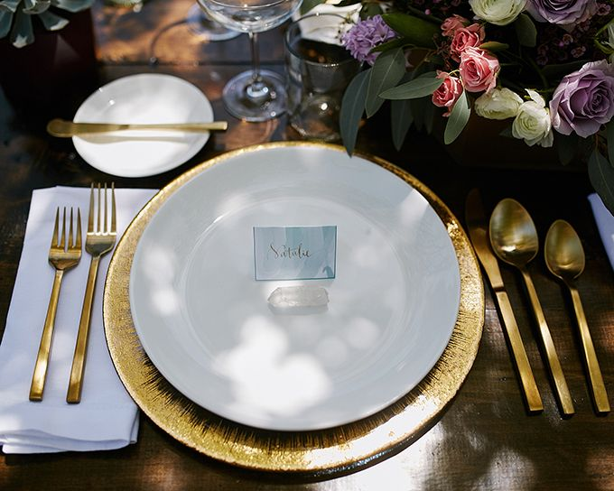 The table setting features gold tableware chargers various flowers and\u2026 & The table setting features gold tableware chargers various flowers ...
