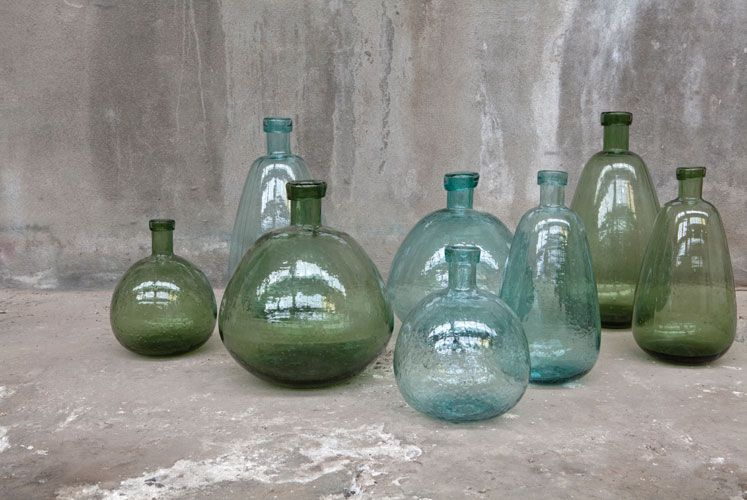 8 green and blue bottles sitting on the floor deco