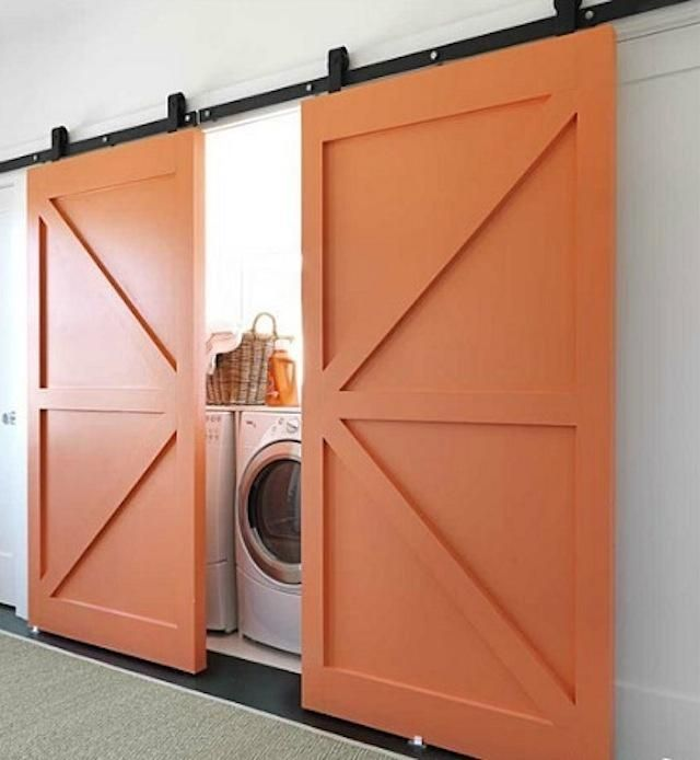 Laundry room with side by side washer-dryer, barn doors.