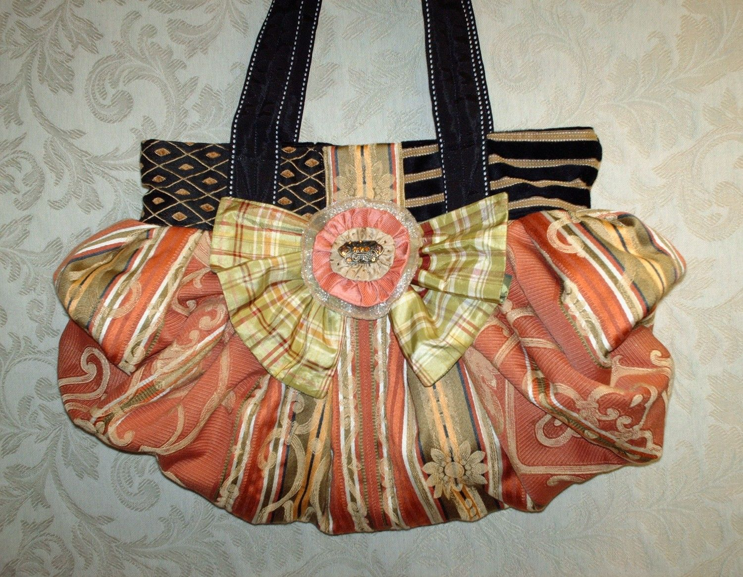 Large Boho Chic Carpet Bag In Tangerine Coral Green And Black With Silk Bow And Handcrafted Removable Brooch. $275.00, via Etsy.