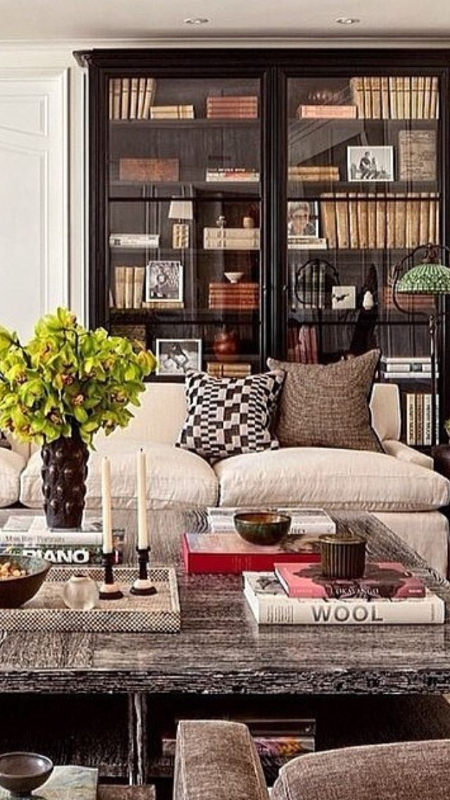 wall glass living room tables. glass front bookcase  cushy linen sofa big coffee table subdued neutral palette