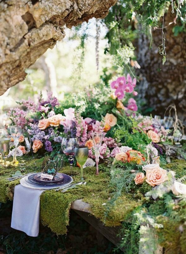 Moss-covered table with stunning floral arrangements. Gorgeous tablescape for a woodland wedding!
