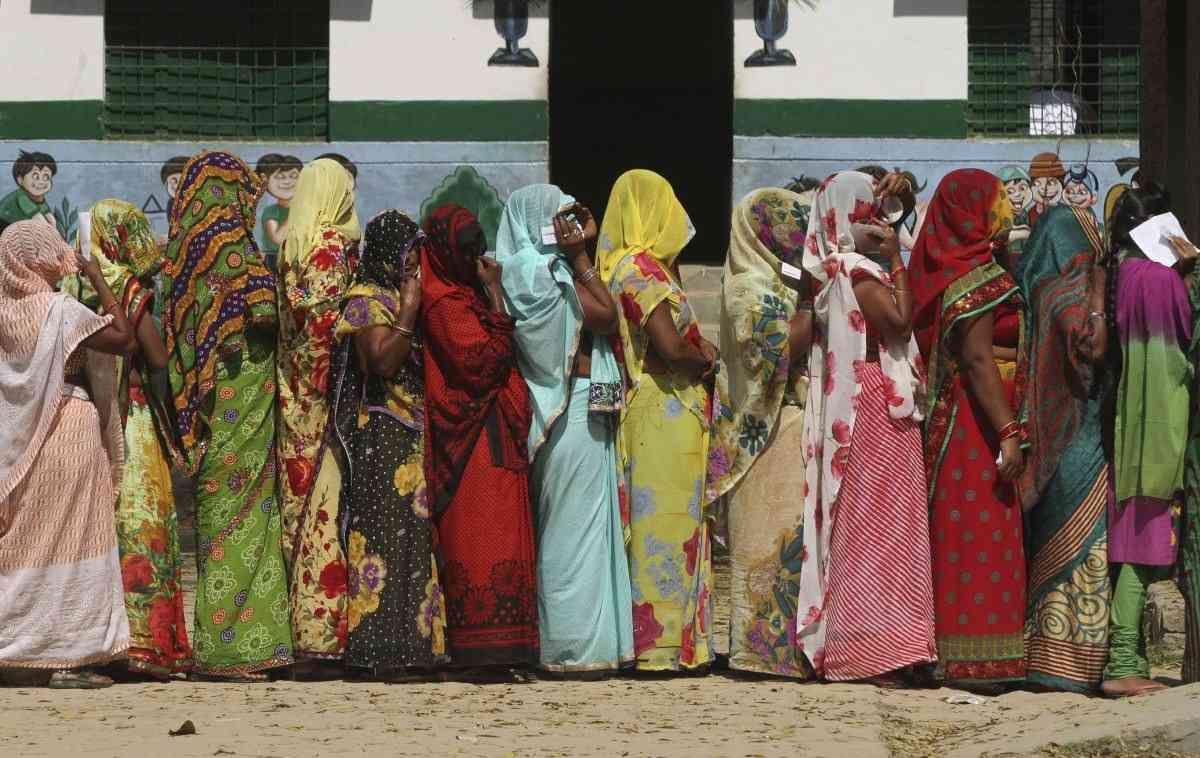 Las mujeres hindúes rurales con sus caras cubiertas se colocan en una cola para emitir sus votos en una mesa de votación en las afueras de Allahabad, estado de Uttar Pradesh, India