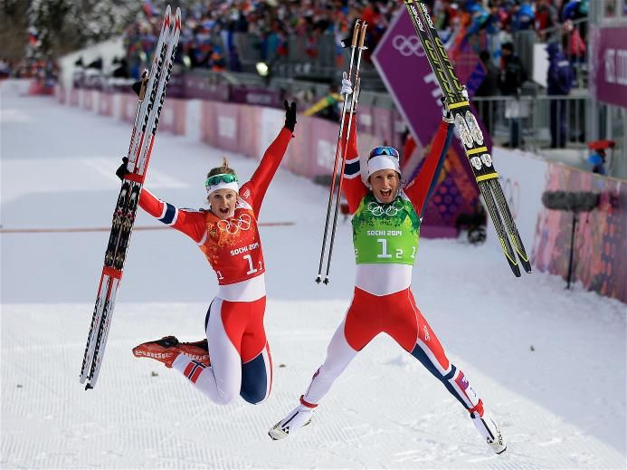 Gold medalists Marit Bjoergen (R) and Ingvild Flugstad Oestberg, of Norway, celebrate after the Women's Team Sprint Classic Final, during Day 13 of the Sochi 2014 Winter Olympics at Laura Cross-Country Ski & Biathlon Center. Sochi 2014 Day 13 - Cross Country Ladies' Team Sprint Classic Final. © 2014 XXII Winter Olympic Games.