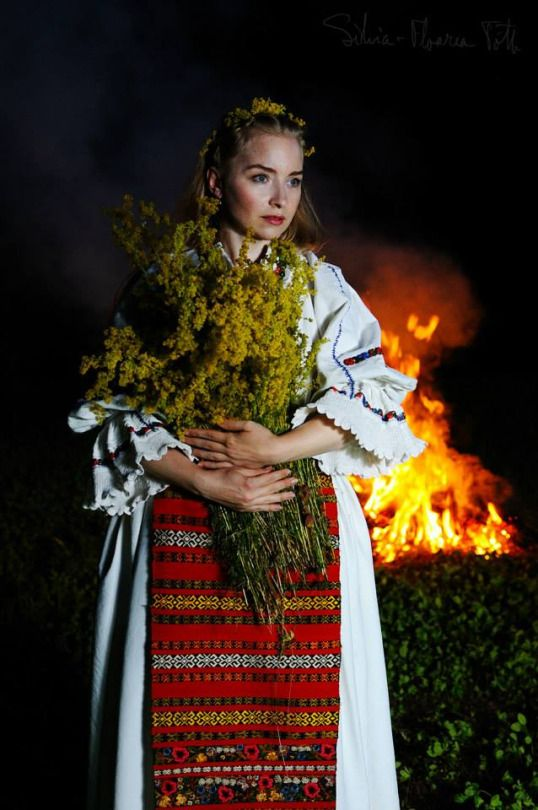 Young Woman in Romanian Traditional Costume holding Sanziene ( Lady's Bedstraw flowers) source :'Colectia de arta populara Silvea-FloareaToth