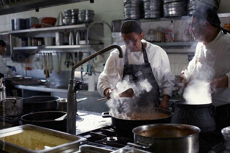 Two chefs at work in a restaurant kitchen by Miquel Llonch