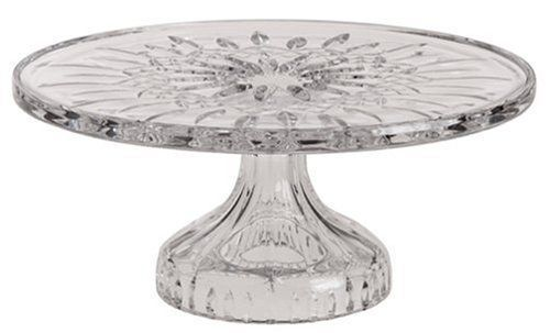 This lavish footed crystal cake plate is part of Waterford's Lismore series. Waterford has been making renowned crystal pieces for more than 200 years and has named many of its patterns after towns in Waterford and other neighboring counties. The Lismore design features repeating leaf motifs for a lively, natural look.