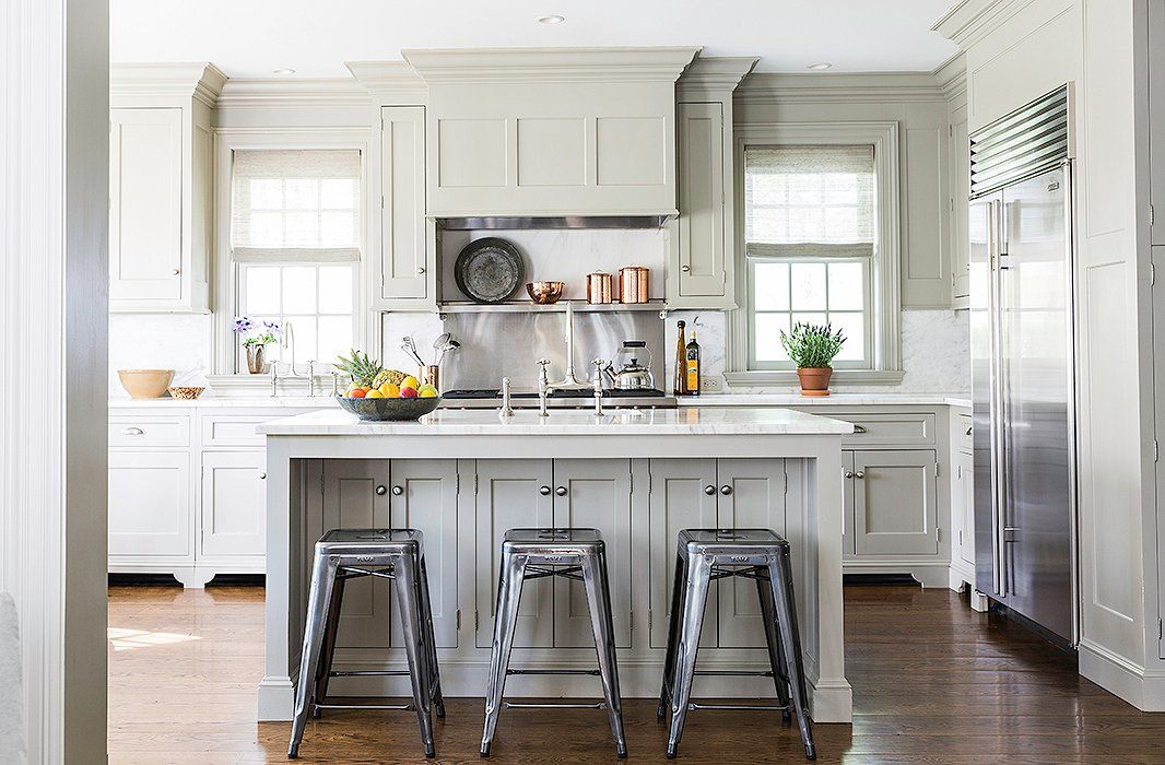 Painted aFarrow & Ball green, the kitchen features a Sub-Zero refrigerator, a Wolf range, Perrin & Rowe sink fittings, and marble countertops and backsplash.