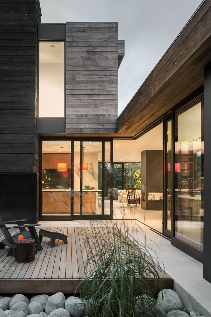 This modern house has operable glass walls that connect the interior spaces with the courtyard and allow the courtyard to become one of the main gathering