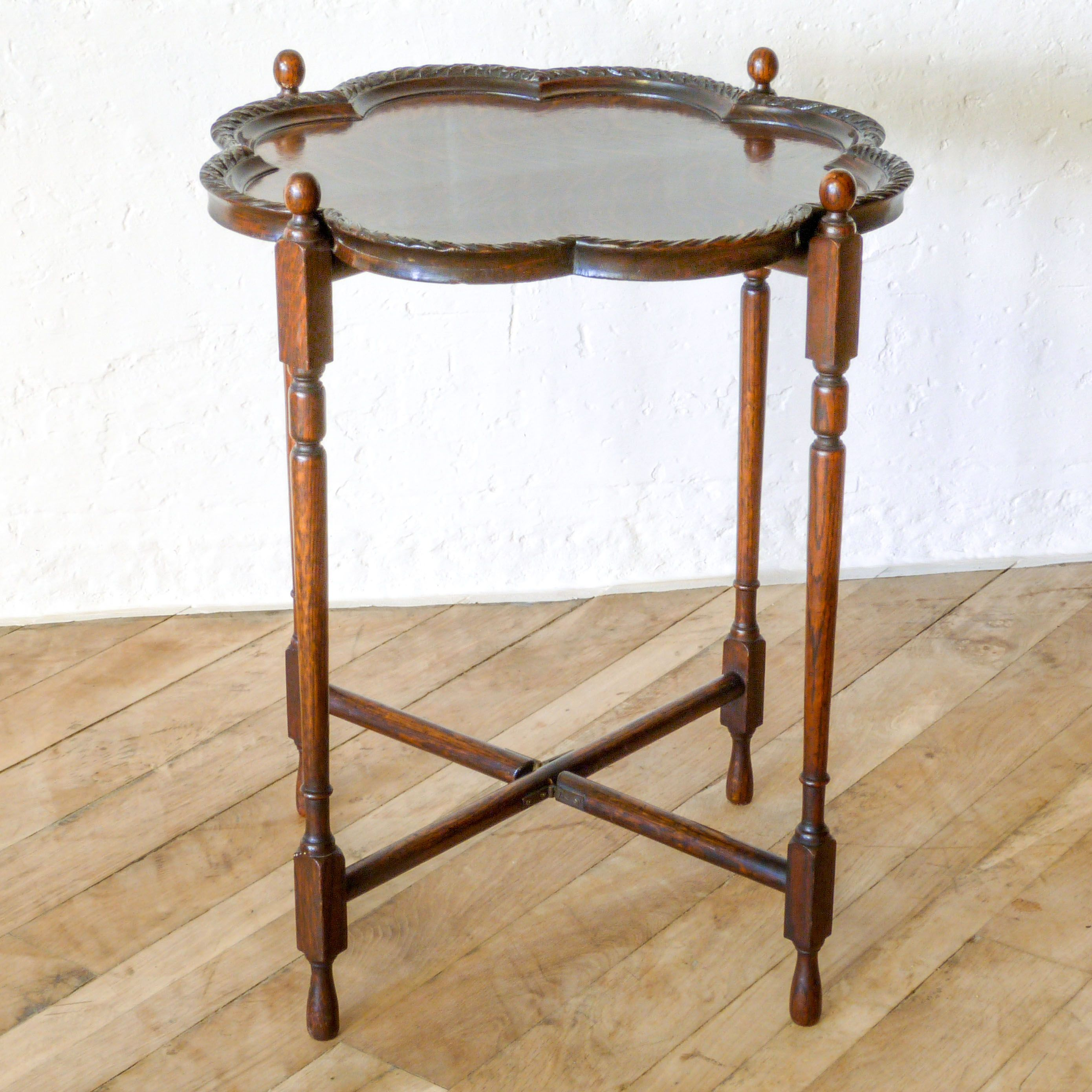 a 1920 s small oak folding table with scalloped edge and crisply