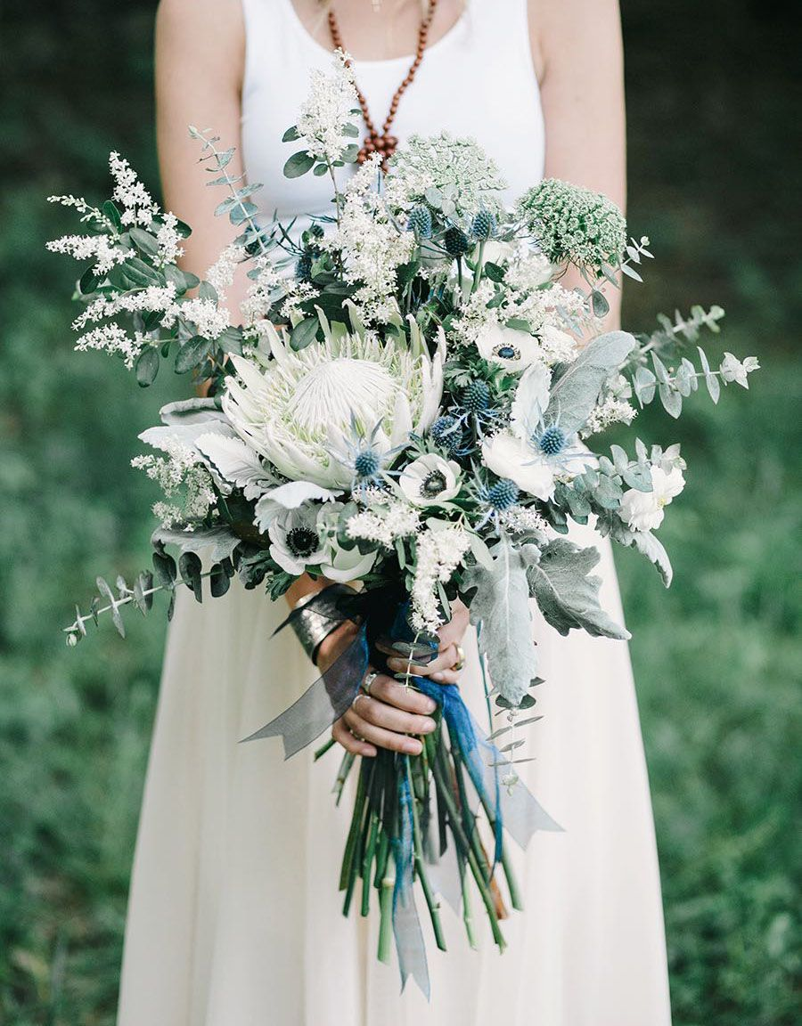 Indie indigo wedding ideas inspired by bonnaroo the bouquet incredible wedding bouquet featuring blue eryngium thistle king protea white anemones several varieties of eucalyptus greenery foliage izmirmasajfo