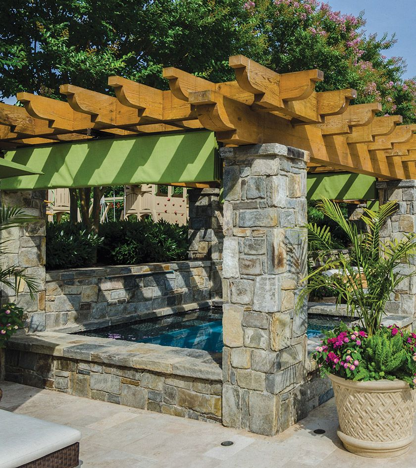 Stone columns support a cedar pergola that shelters the ... on Colao & Peter Luxury Outdoor Living id=50451