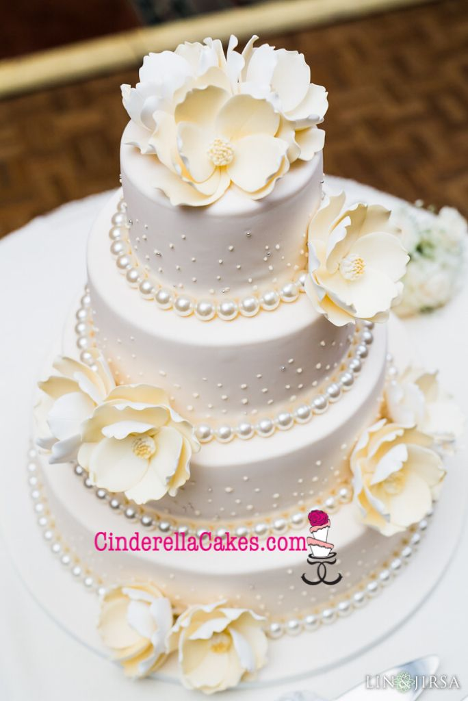 Beautiful gumpaste flowers with pearlized fondant balls at the base of each tier