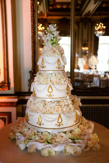 A stunning white and gold wedding cake with lots of details