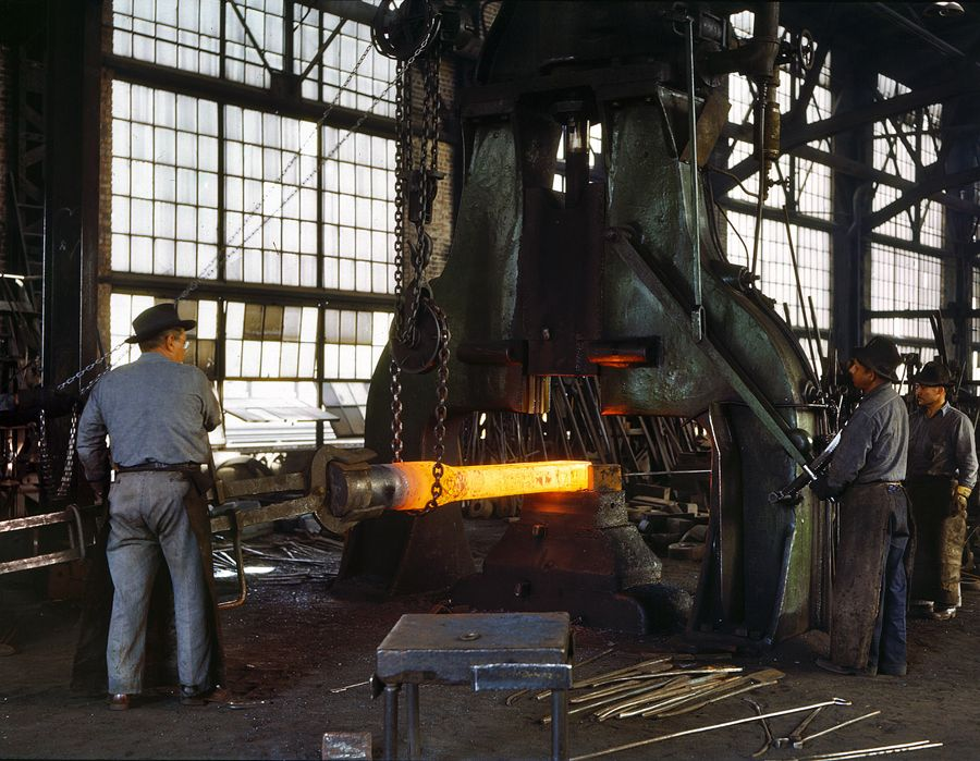 """March 1943. """"Santa Fe R.R. shops, Albuquerque. Hammering out a drawbar on the steam drop hammer in the blacksmith shop."""" 4x5 Kodachrome transparency by Jack Delano for the Office of War Information."""