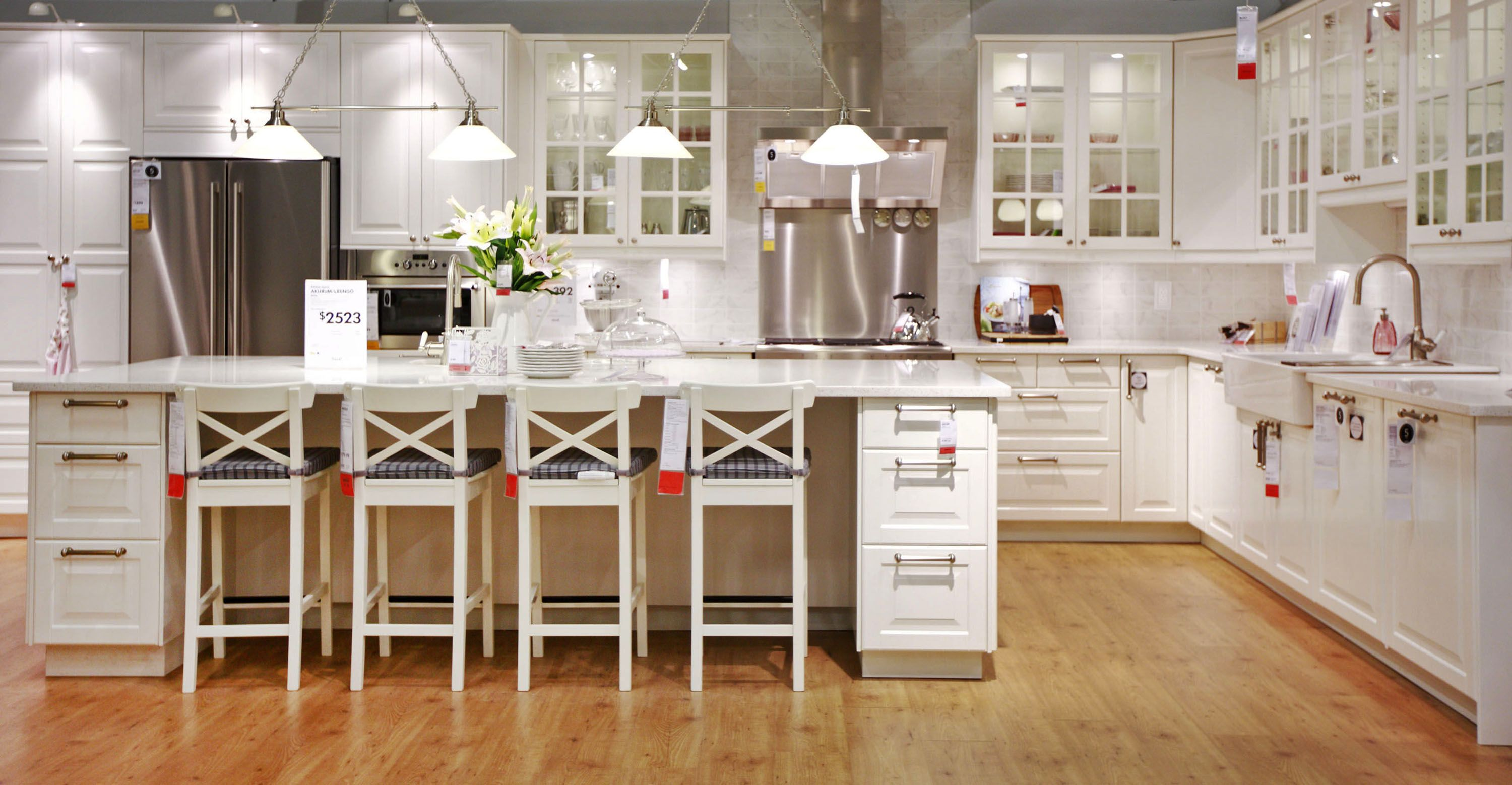 Luxurious White Wooden Ikea Kitchen Cabinets On Cool Brown Laminating Flooring With Large White Island And
