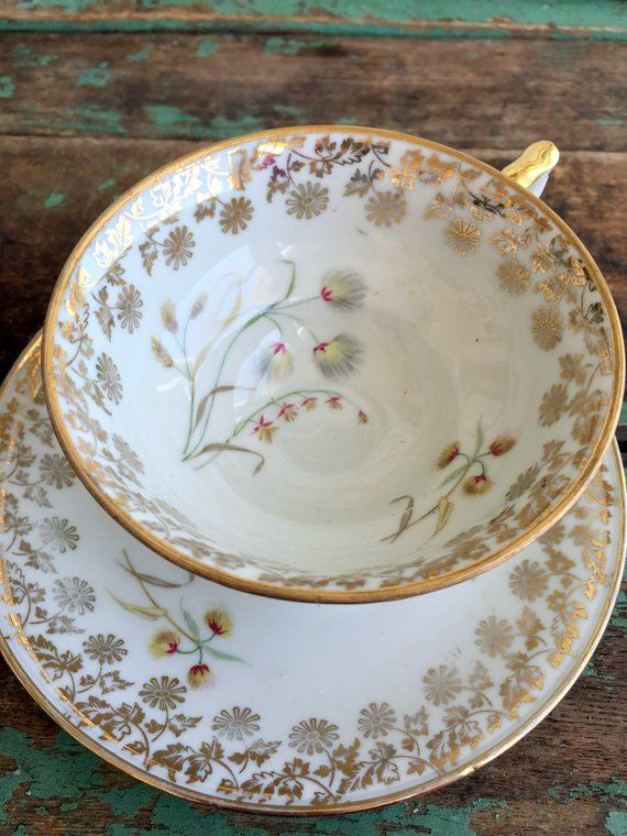 Antique white and gold cup and saucer