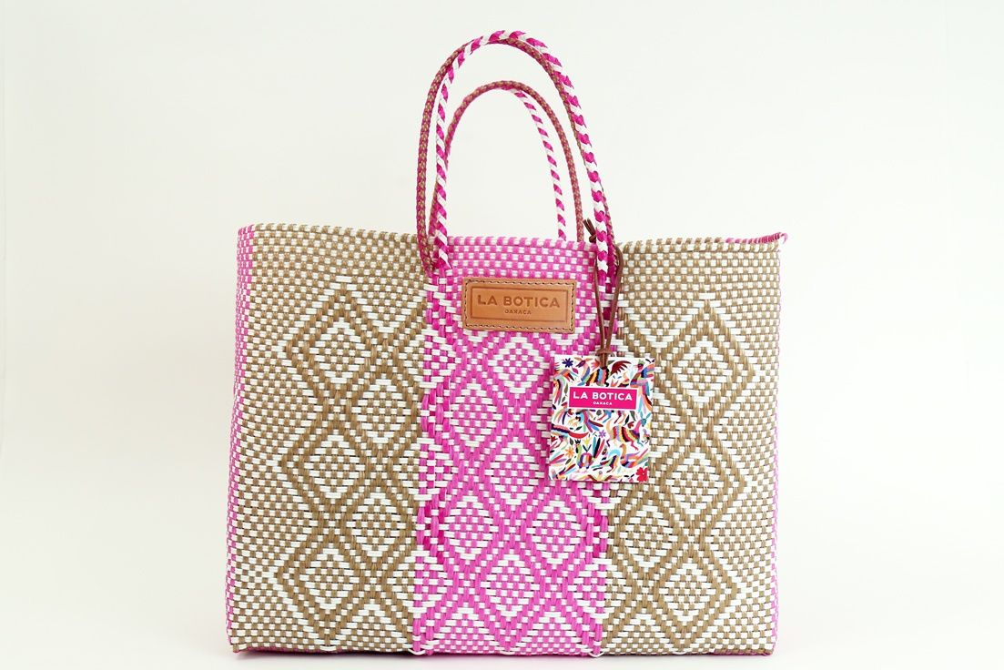 A beautiful, handwoven pink and brown tote bag by artisans in Mexico's Oaxaca province, known for its bright colors and intricate design. Versatile and durable - bring this to the market or beach!