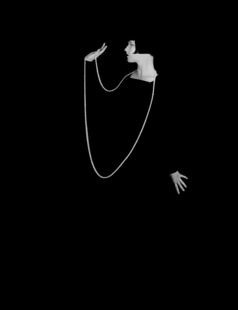 1929: American actress Louise Brooks (1906 - 1985) wearing a long necklace which stands out starkly against a black background. // Photo by Eugene Robert Richee