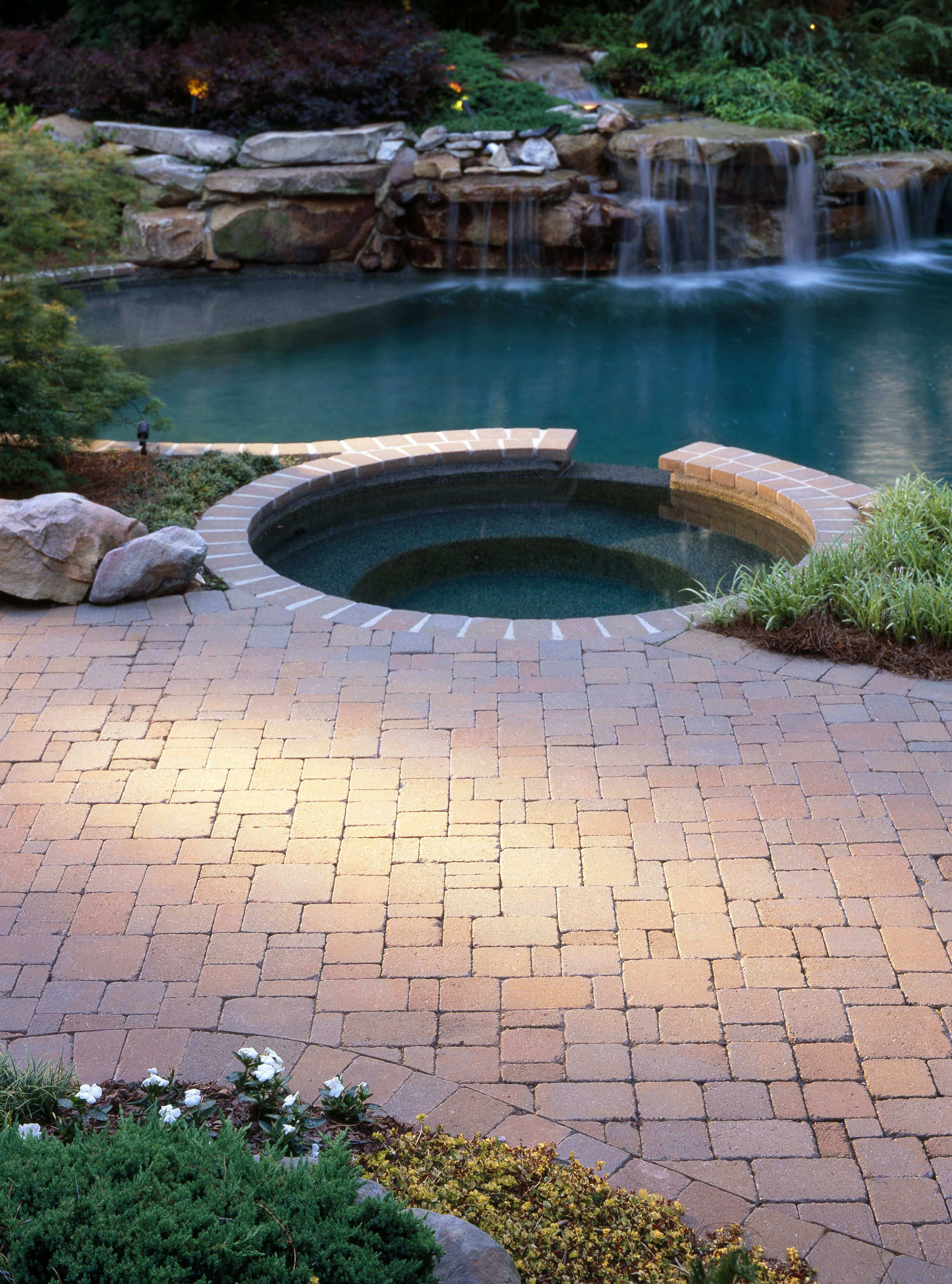 Red Paver Pool Deck And Hot Tub With Natural Stone Waterfall And Landscaping Brick Pavers Pool Deck Paver Tiles
