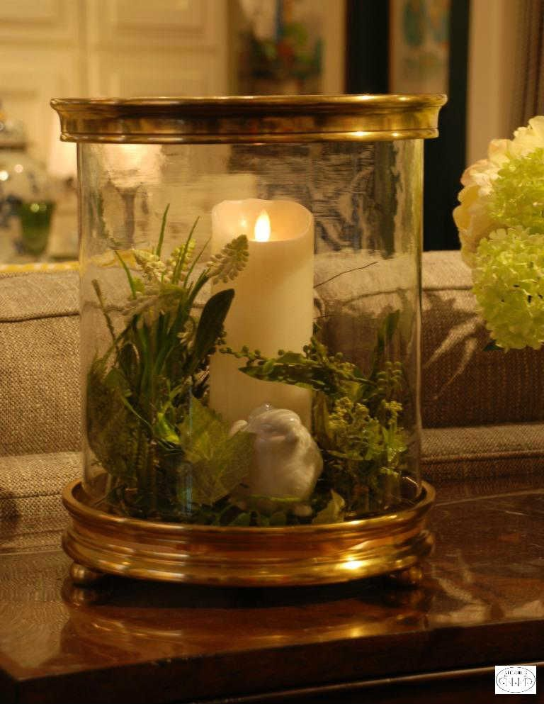 To add a touch of spring to your decor, fill a hurricane with greens and a bird figurine.