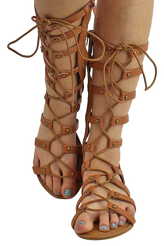 Rustic studs highlight the slender straps of an attention-grabbing gladiator sandal detailed with crisscrossing laces up the front shaft. Shoe measures 12 inches from bottom of heel to top edge. Heel