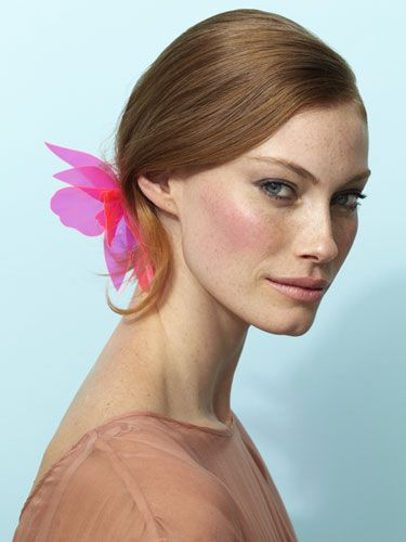 First, swirl a blush you can actually see on the apples of your cheeks; poppy pink works on every skin tone. Then, tuck a flashy-pretty clip or comb into the side of a low bun.