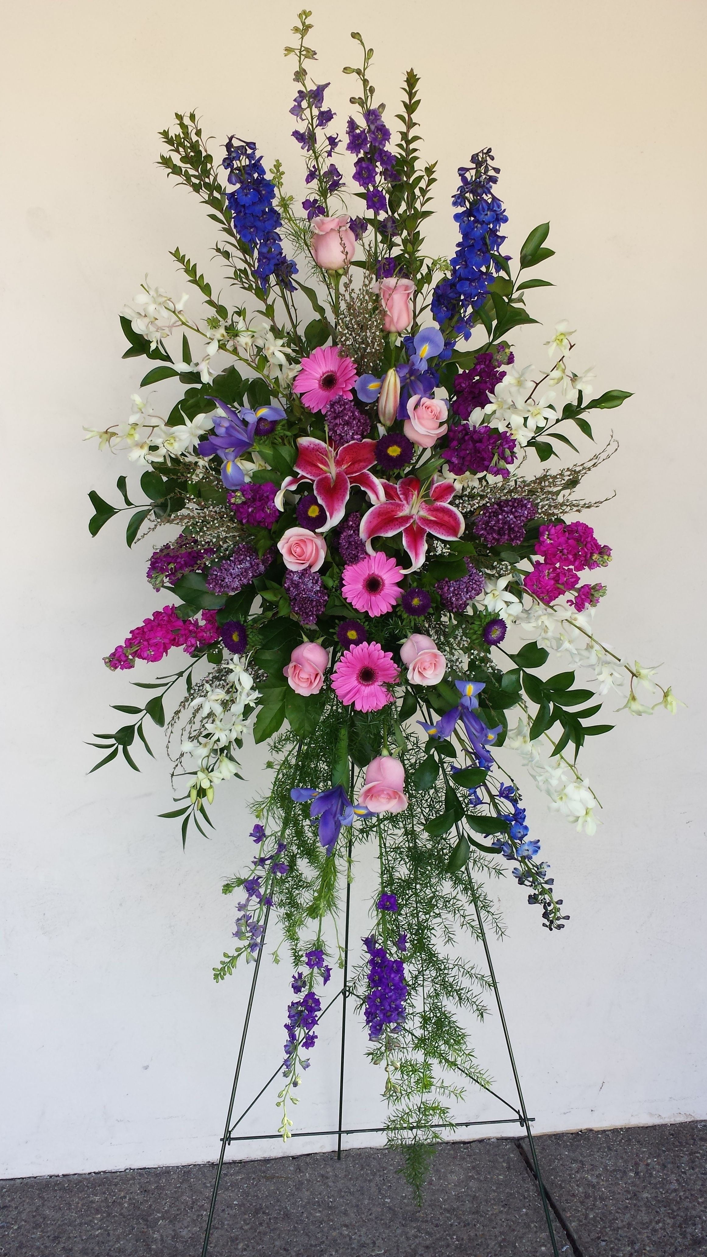Standing funeral spray of stargazer lilies blue delphinium purple standing funeral spray of stargazer lilies blue delphinium purple larkspur pink gerbera daisies pink roses stock lilac iris and white hawaiian izmirmasajfo