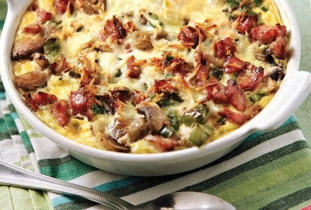 Υλικά Συνταγής 8 φέτες ψωμί του τοστ 2 λουκάνικα ψιλοκομμένα 1 κρεμμύδι ψιλοκομμένο 2 πιπεριές ψιλοκομμένες 2 φλ. μανιτάρια κομμένα στα τέσσερα 1 ½ φλ. γραβιέρα τριμμένα 7 αυγά ½ φλ. γάλα 2 κ.σ.