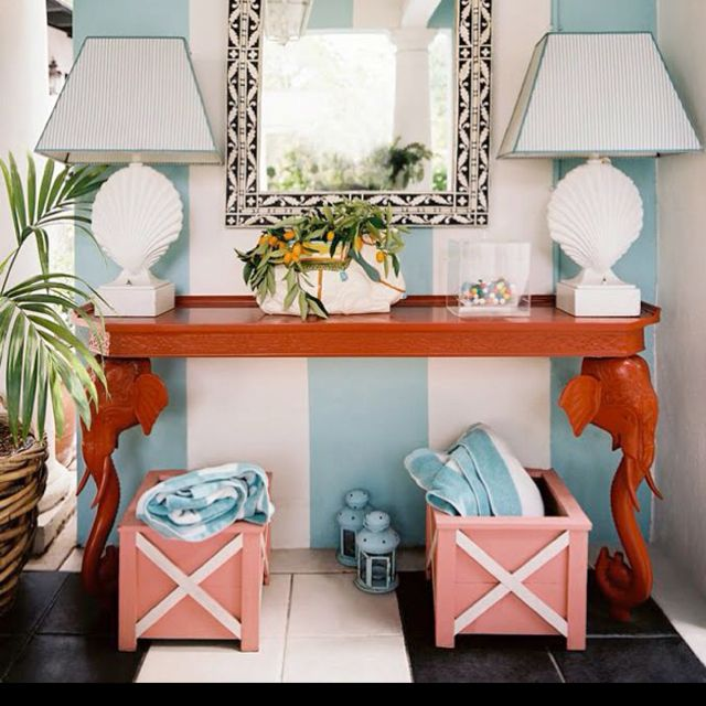 This entryway is awesome on so many levels: elephant busts as the table legs, bold stripes as wallpaper,  creative storage, and awesome yet not too loud seashell lamps.