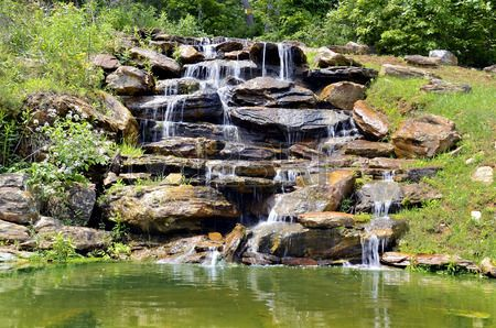 A Small Natural Looking Man Made Waterfall For Landscape Design Stock Photo