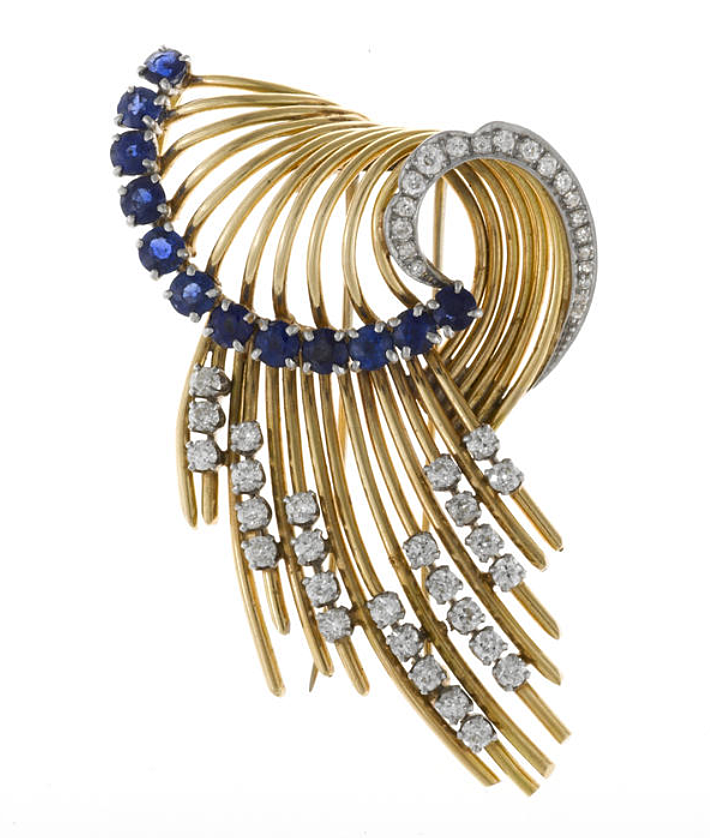 A retro sapphire and diamond brooch, circa 1950  estimated total round-cut sapphire weight: 2.00 carats; estimated total diamond weight: 1.90 carats; gross weight approximately: 26.5 grams; mounted in platinum and fourteen karat gold; length: 2 3/4in.