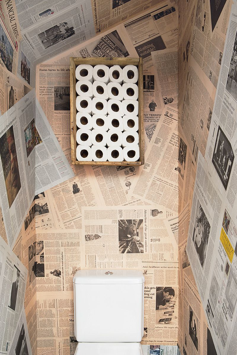 awesome bathroom with newspapers as wallpaper and toilet rolls stock
