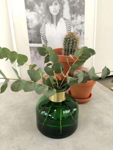 """Fin og dekorativ vase i grønt glass fra danske Nordal. Denne skiller seg ut i mengden og er utrolig fin uansett hvilket uttrykk du styler den med.  MåL: H18cm Diameter 18cm Vekt: 1 kg Laget av: Glass med messing """"ring"""" rundt halsen."""