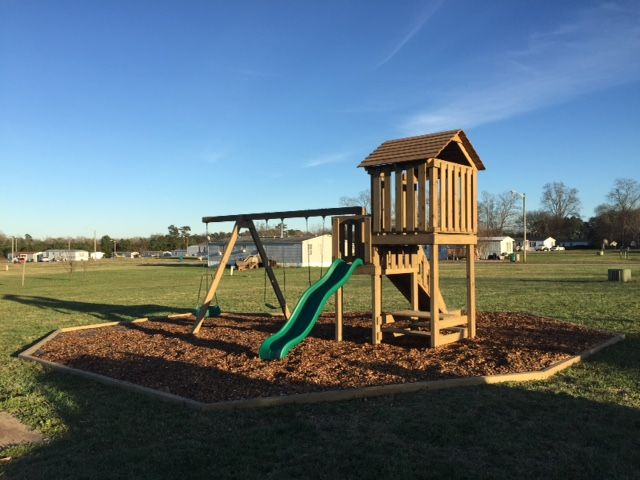 Wooden Outdoor Play Set With Wood Chip Ground Cover And Edging The