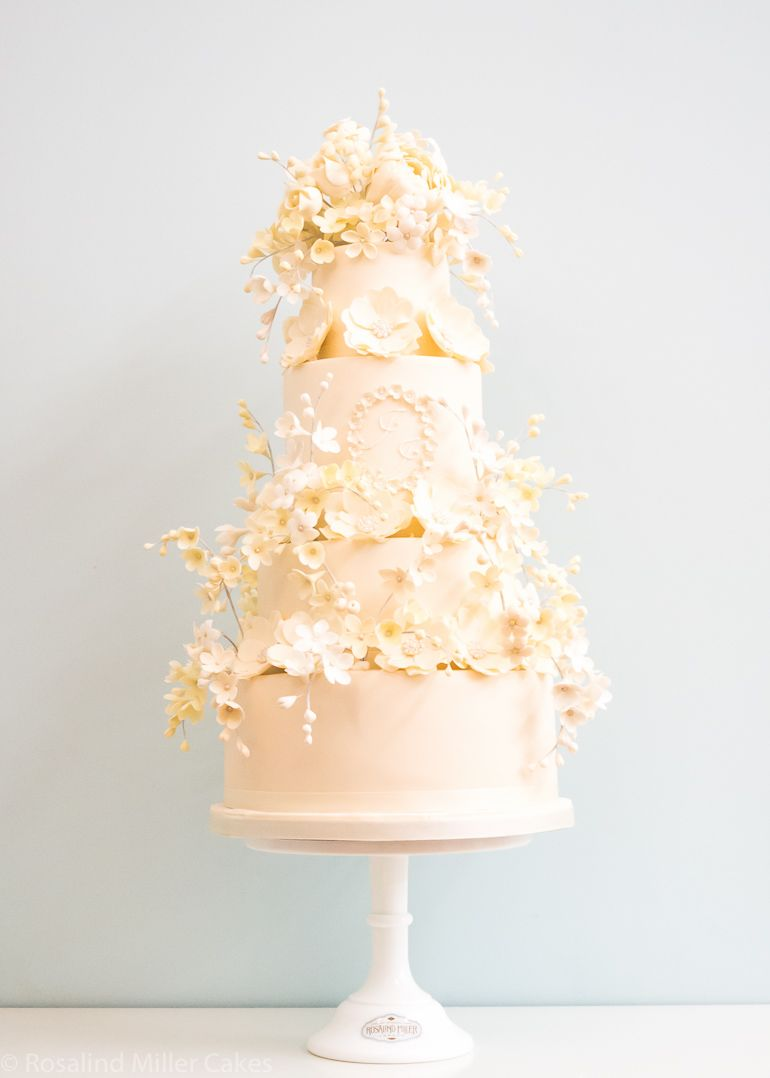 This elegant 4 tier wedding cake features sprays of ivory and cream ...