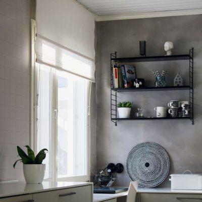 Musta String hyllykkö keittiön seinällä tuo mukavasti säilytystilaa arjen tarpeistolle ja koriste-esineille