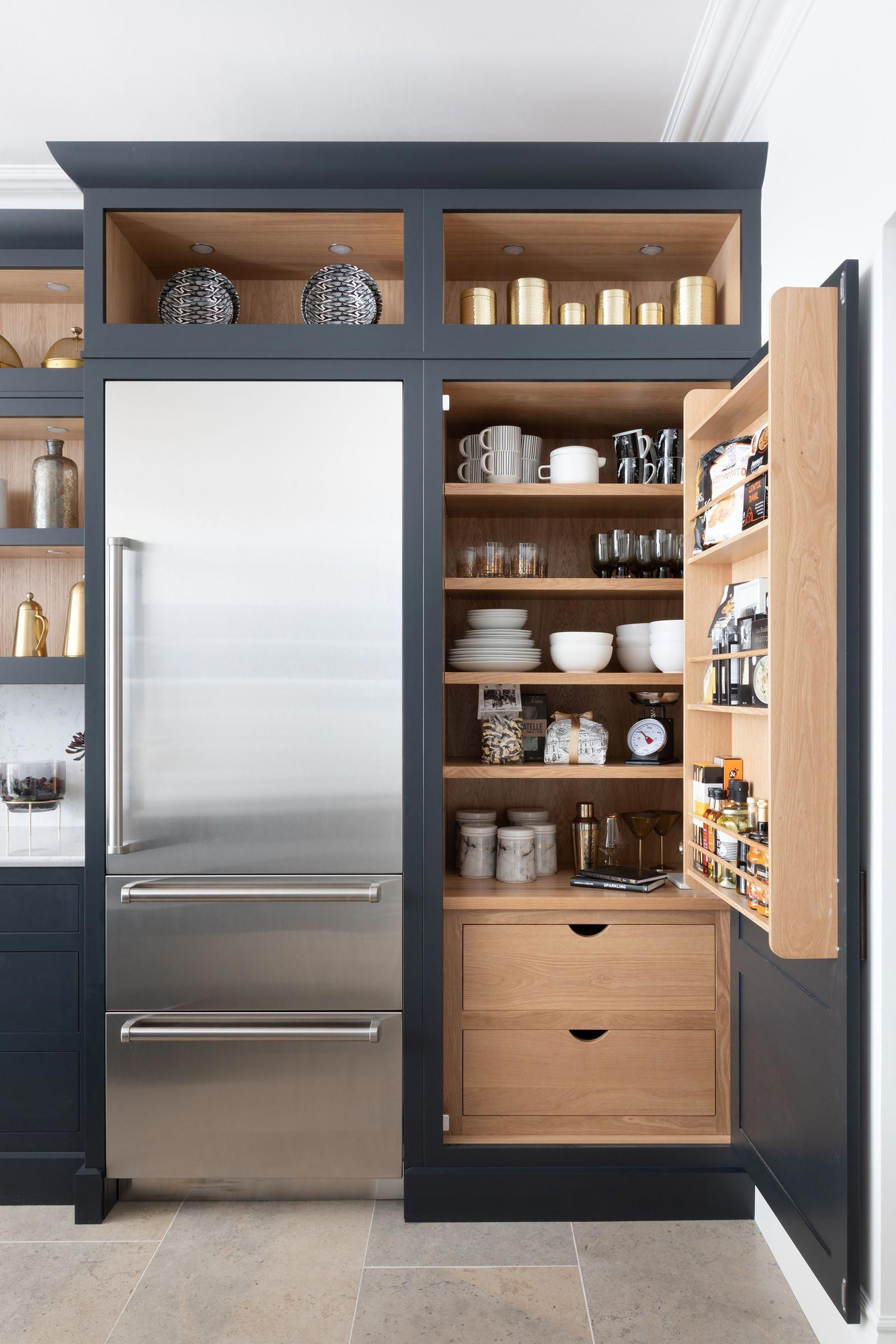 Here, a smart navy grey pull-out larder-style cabinet helps to