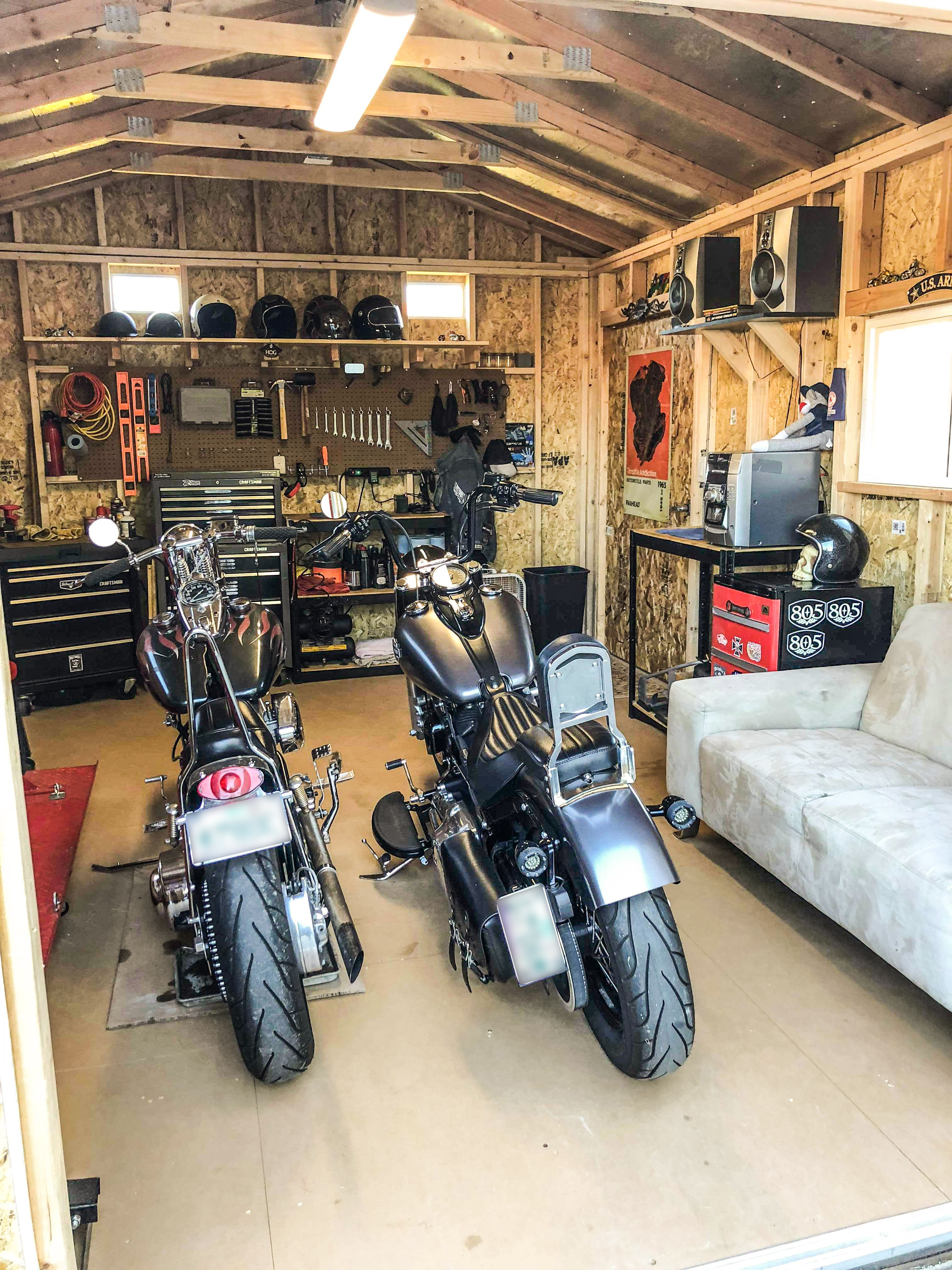 This man cave has it all-a workbench, storage, and a space to hang out after working on the motorcycles. Even better, it cleared out enough space in the garage to park the cars. Double duty and it looks great too! #garagemancaves