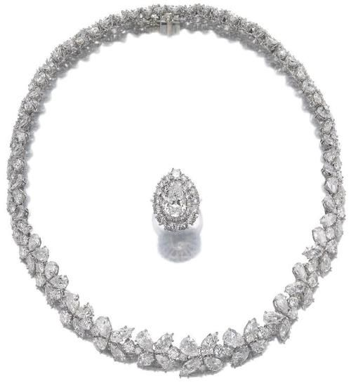 Diamond necklace and a diamond ring.     The flexible necklace of foliate design set throughout with clusters of marquise-, pear- shaped, and brilliant-cut diamonds, length approximately 375mm; the ring set with a pear-shaped diamond, surrounded by brilliant-cut diamonds, size 50.    Sotheby's.